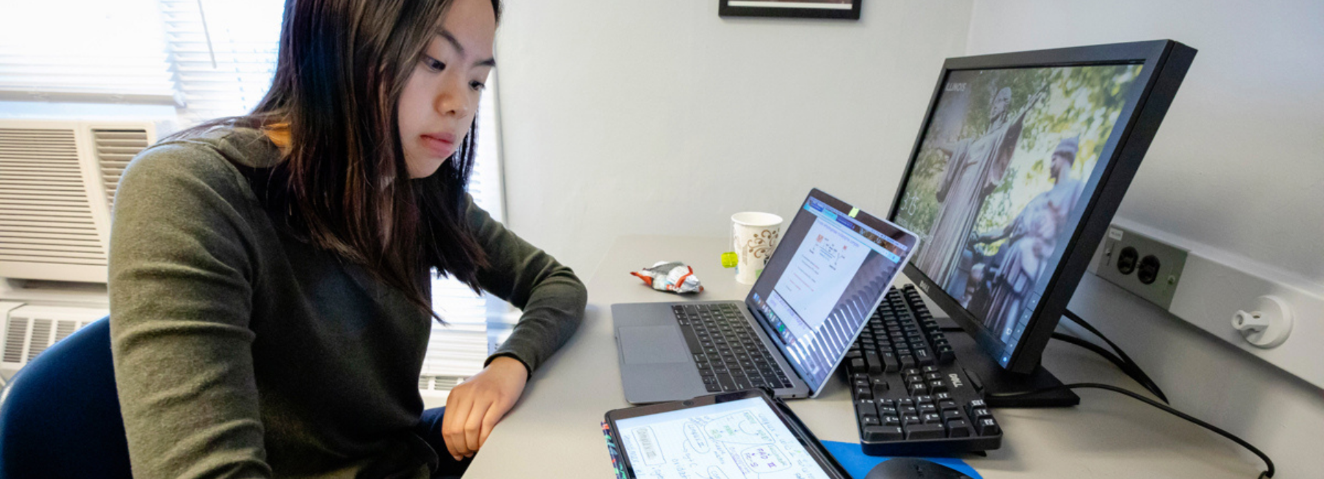 student sits and works at her desk with multiple computer screens