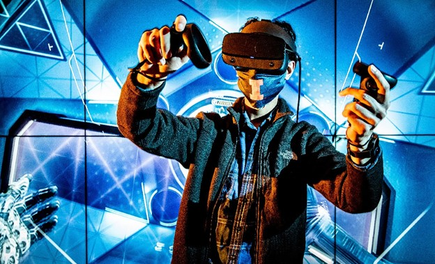 Blue background, person wearing VR mask and holding VR controllers